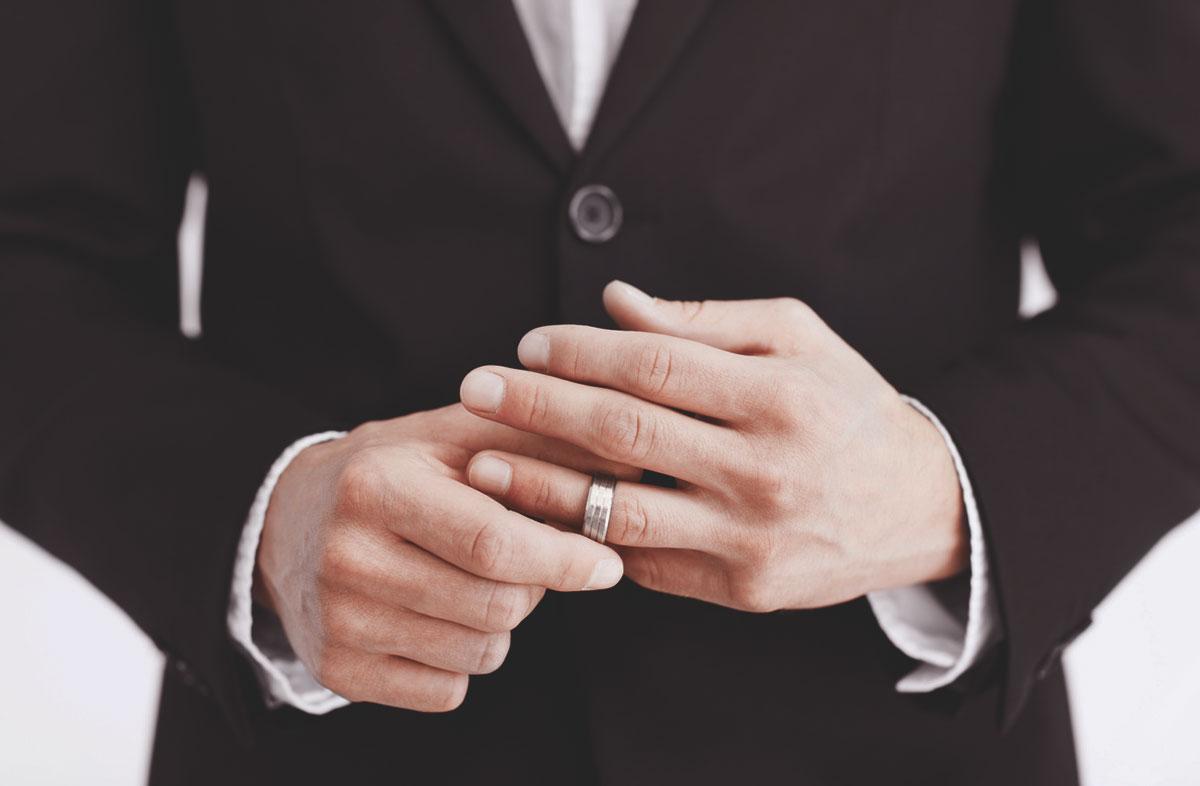 Мужчина в деловом костюме с кольцом из белого золота