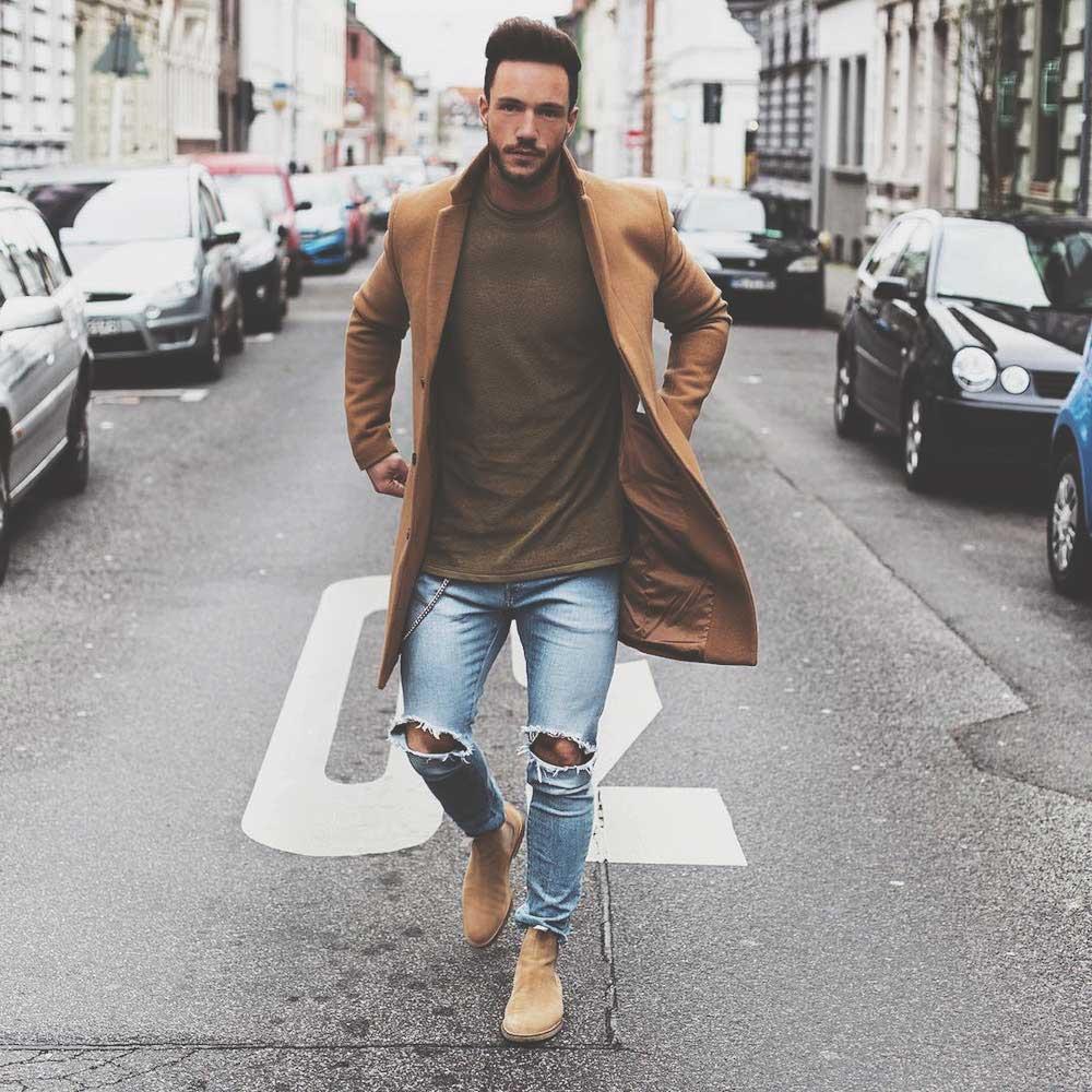 Мужчина в высоких ботинках челси в рваных джинсах и пальто