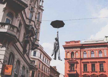 Прага, Чехия. Мужчина в костюме с зонтичной статуей