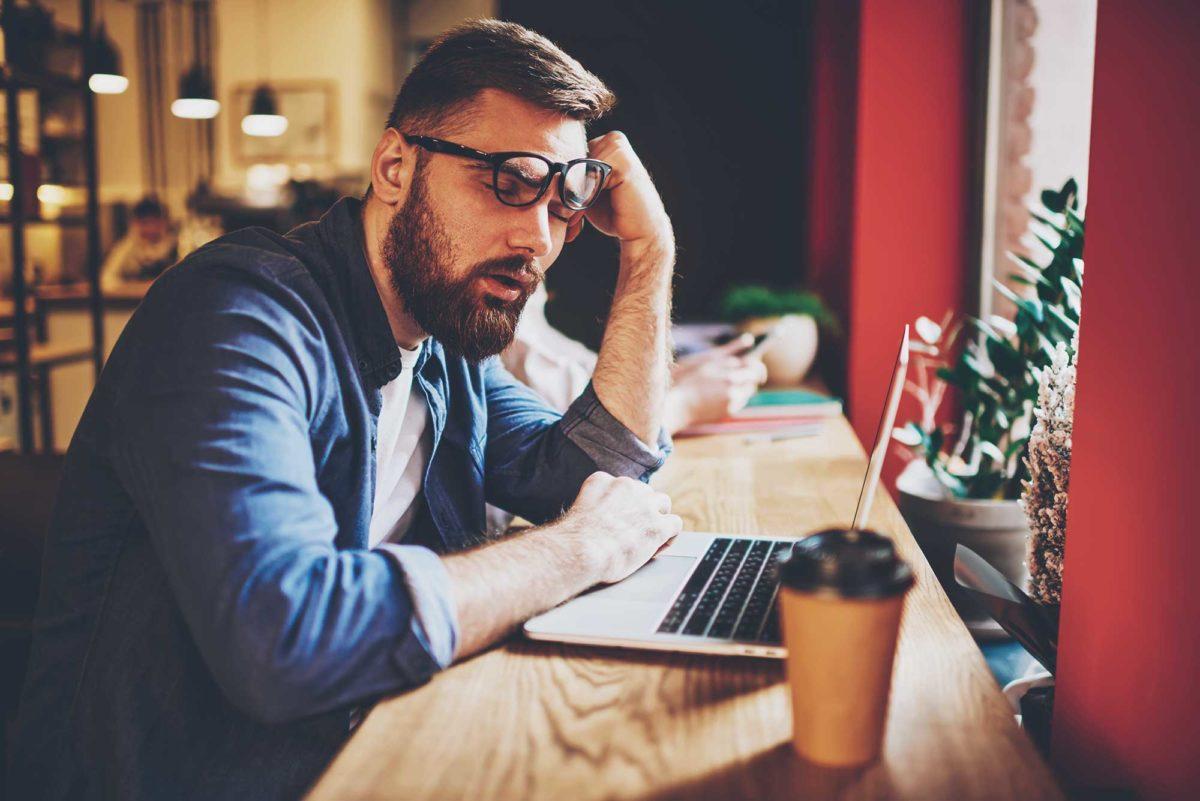 Мужчина дремлет за ноутбуком