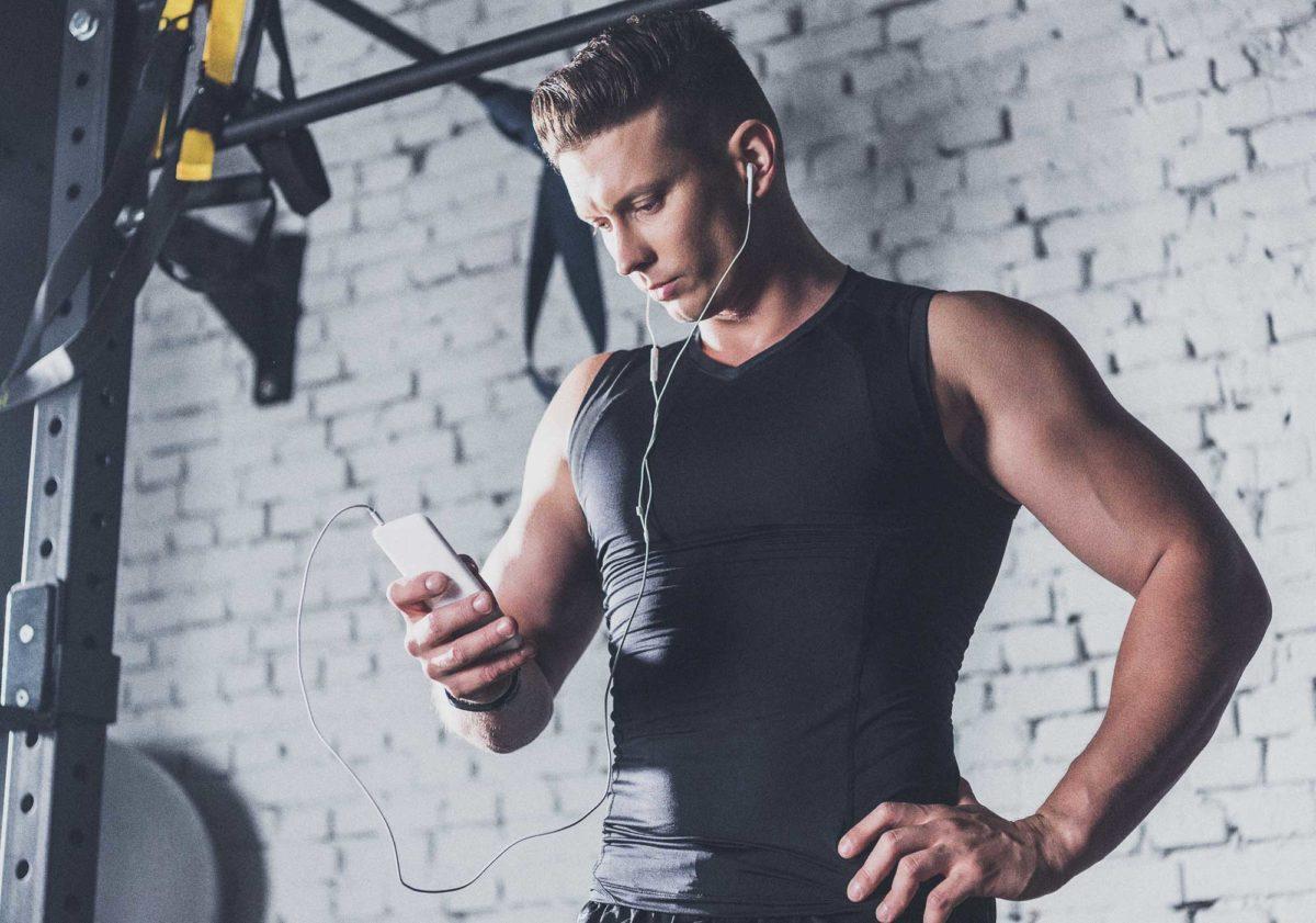 Спортивный мужчина со смартфоном в наушниках