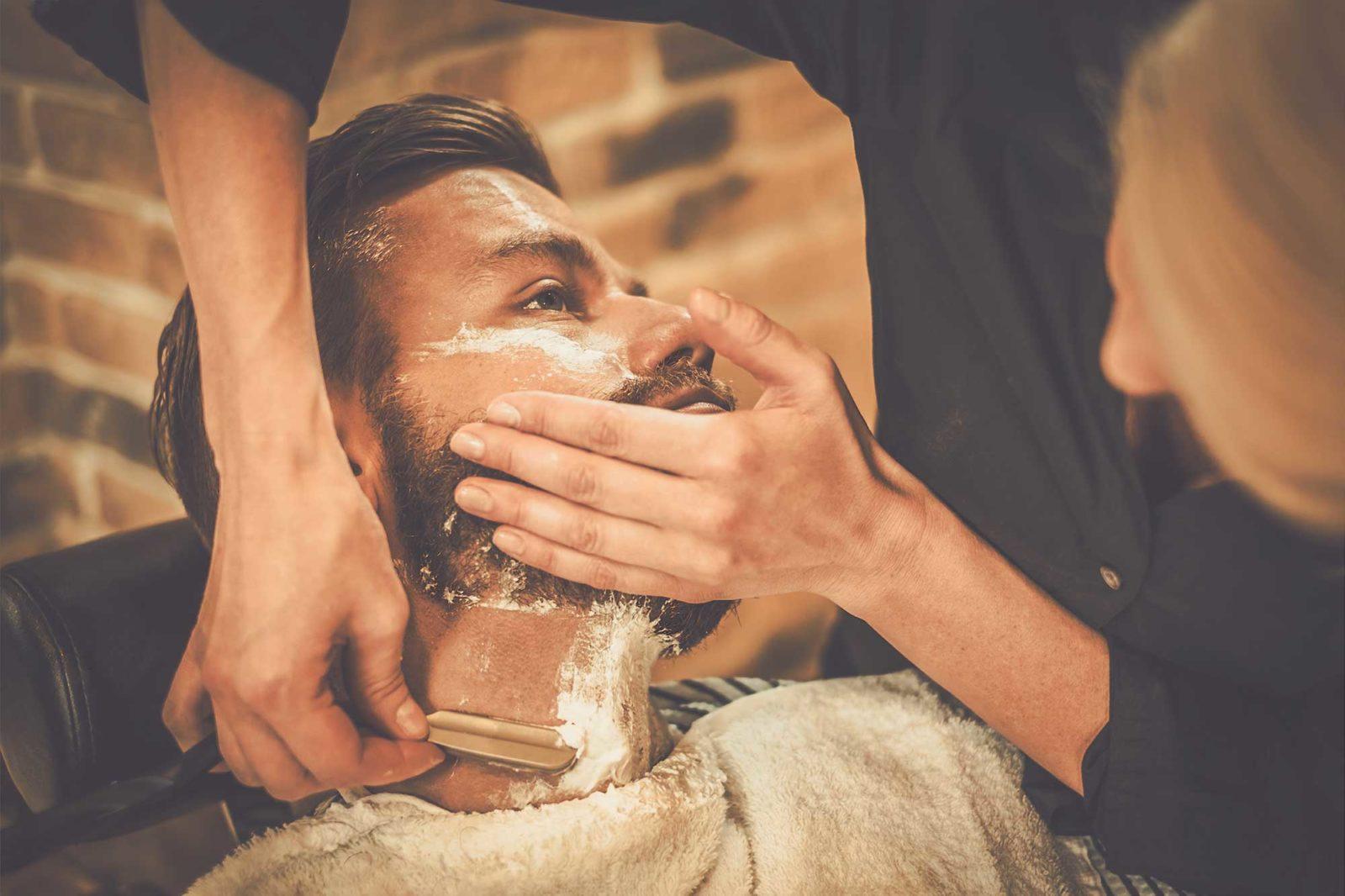 Клиент во время бритья бороды в барбершопе
