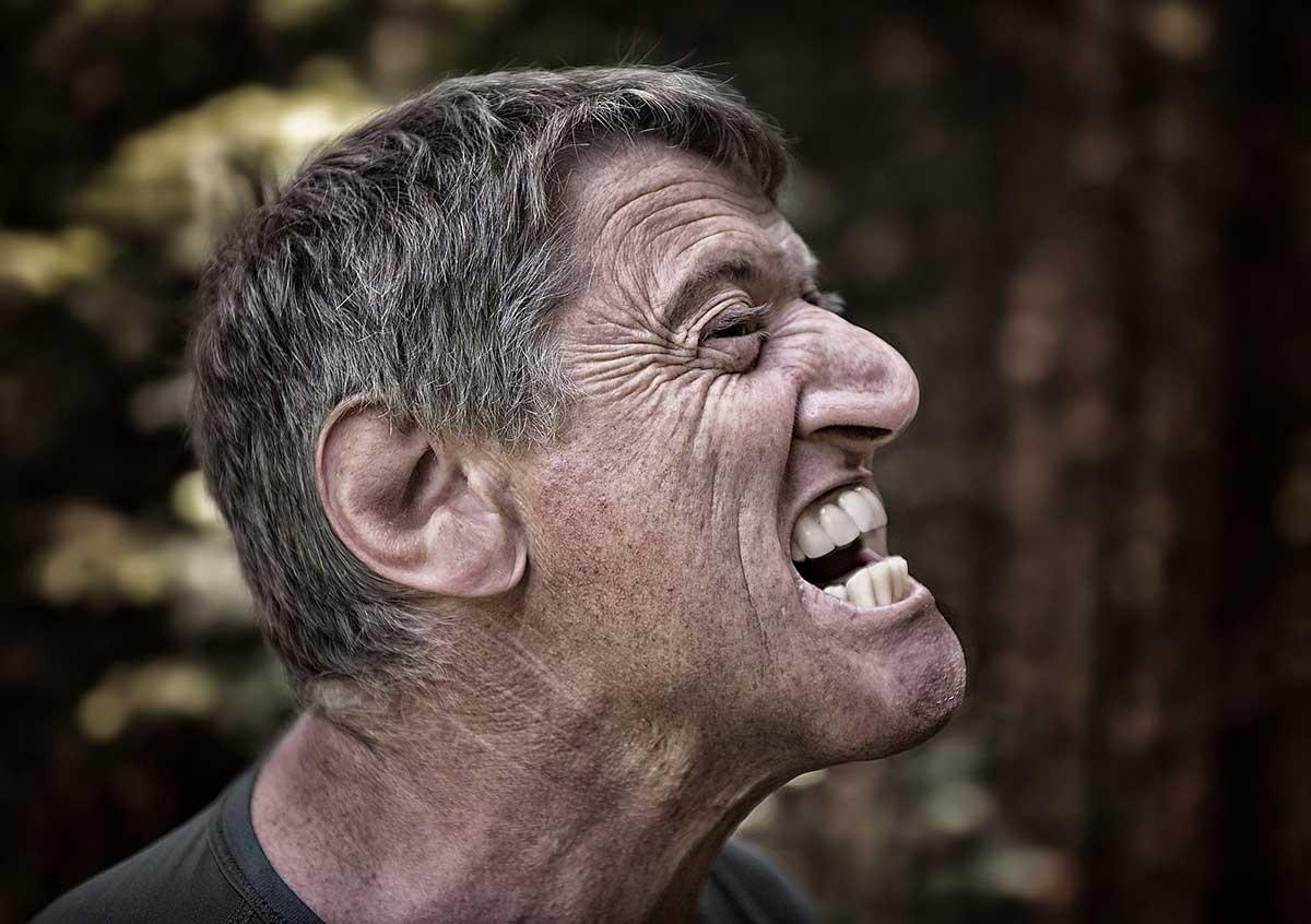 Мужчина дышит неприятным запахом изо рта