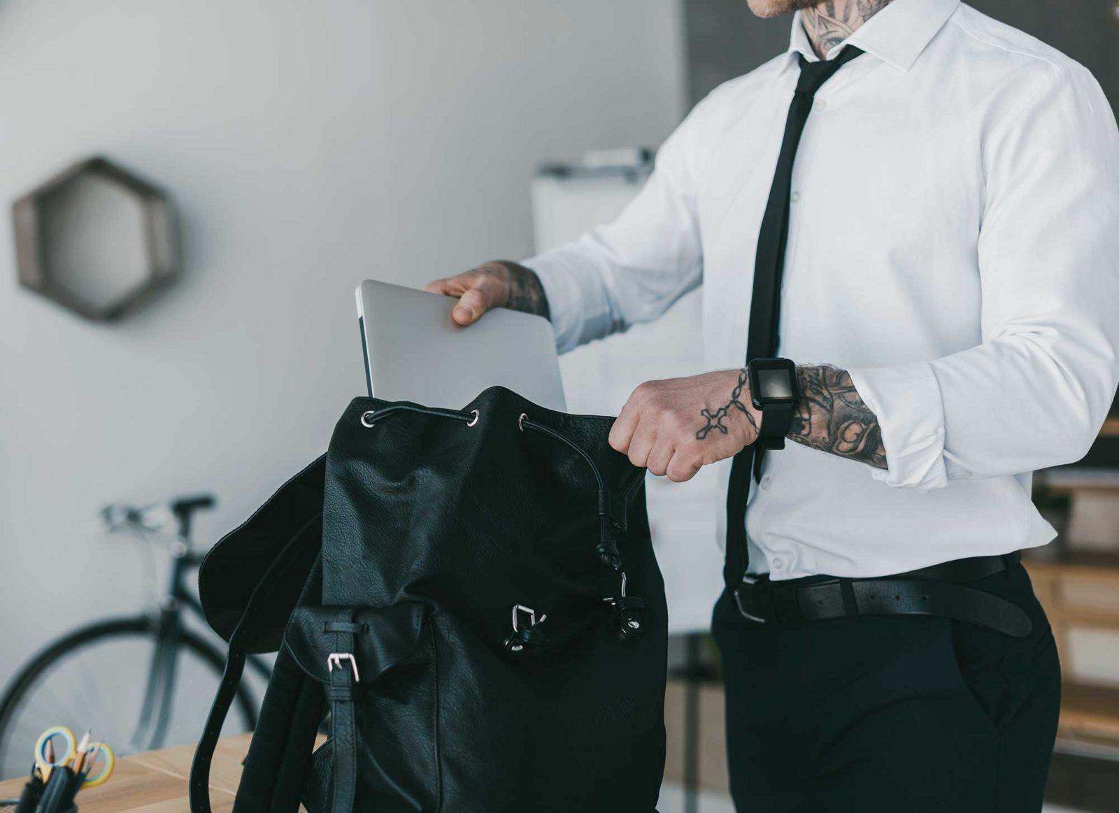 Современный бизнесмен вкладывает ноутбук в рюкзак