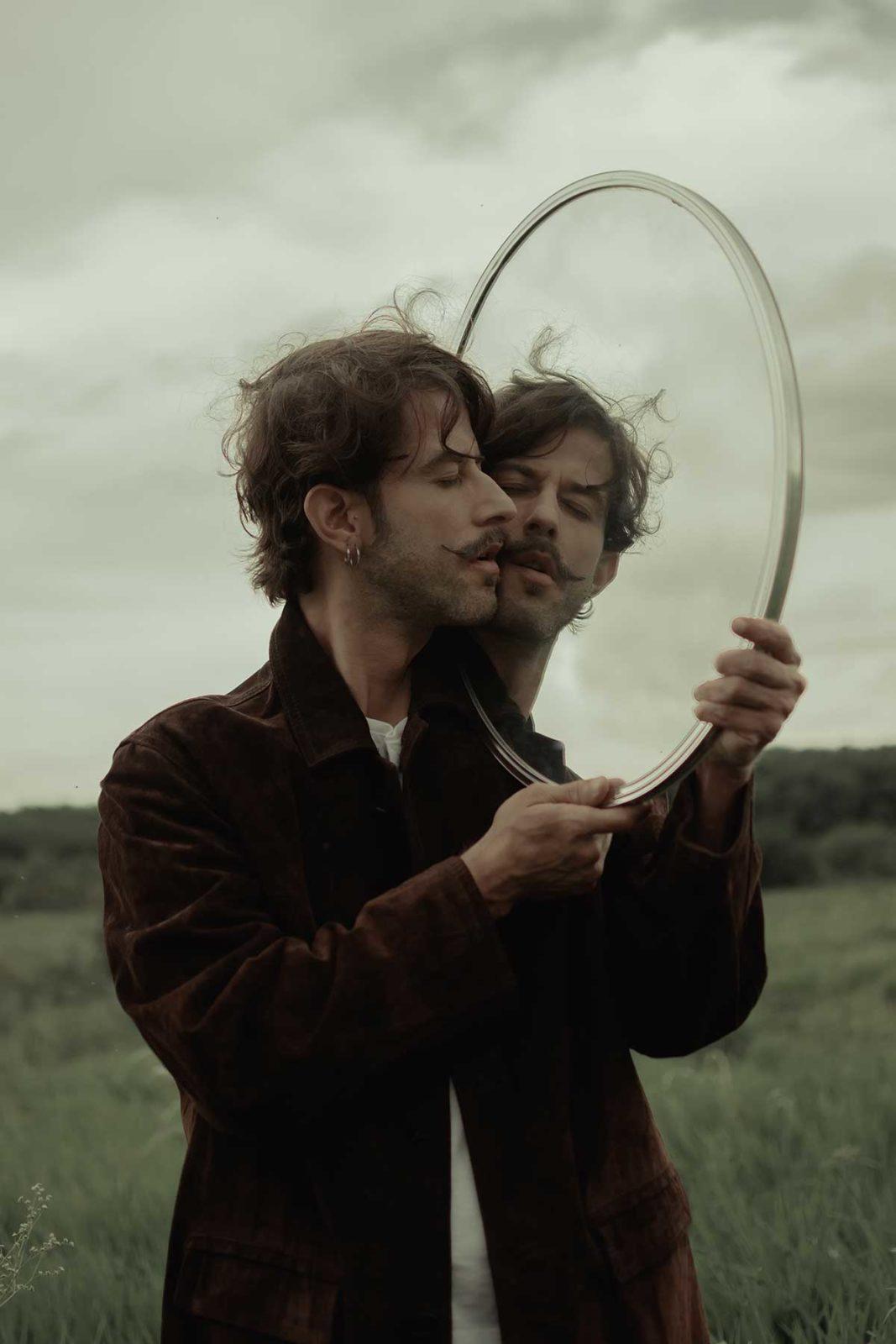 Усатый мужчина смотрит в зеркало