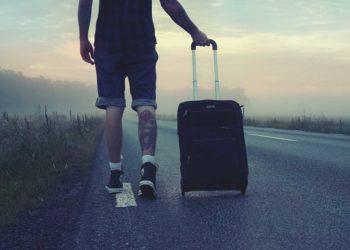 Мужчина турист идущий по дороге с чемоданом