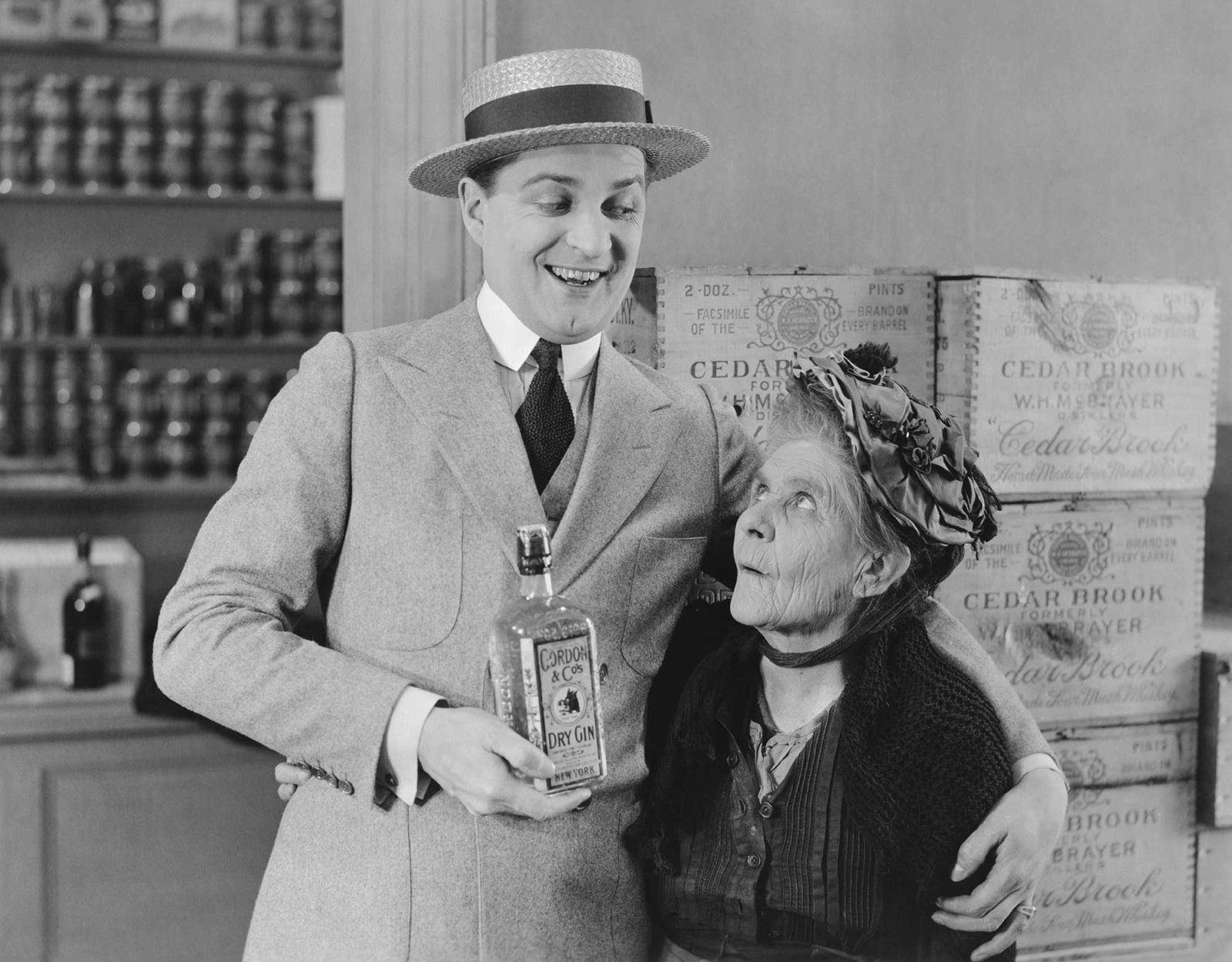 Мужчина в шляпе показывает бутылку джина пожилой женщине