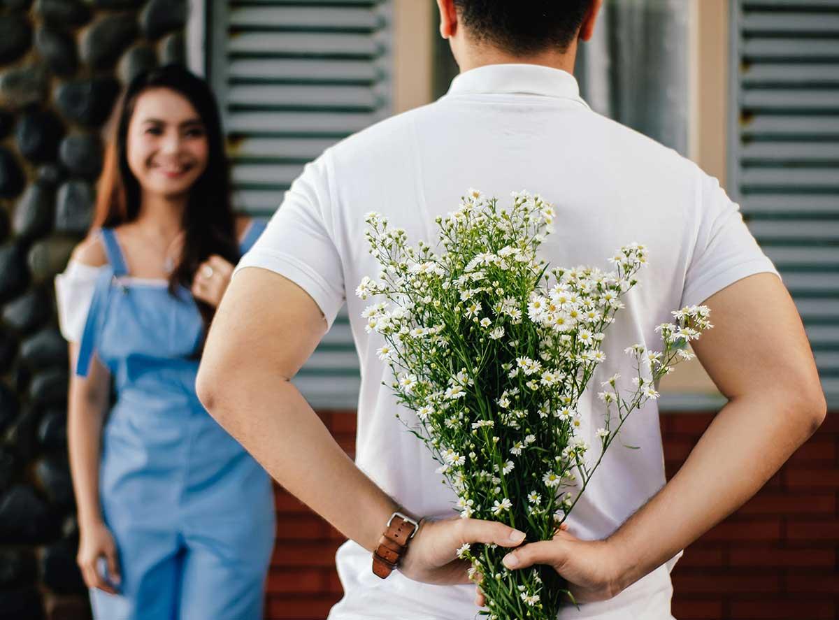 Мужчина дарит букет цветов девушке
