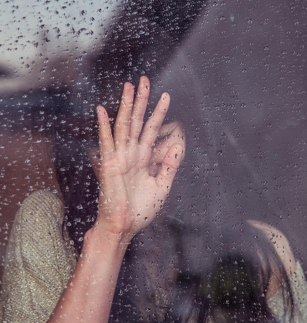 Девушка плачет у окна