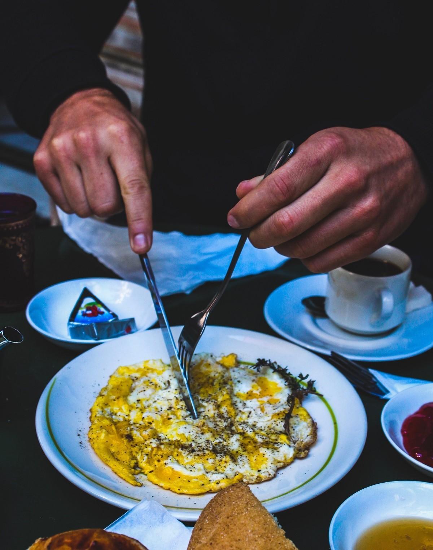 Мужчина ест омлет