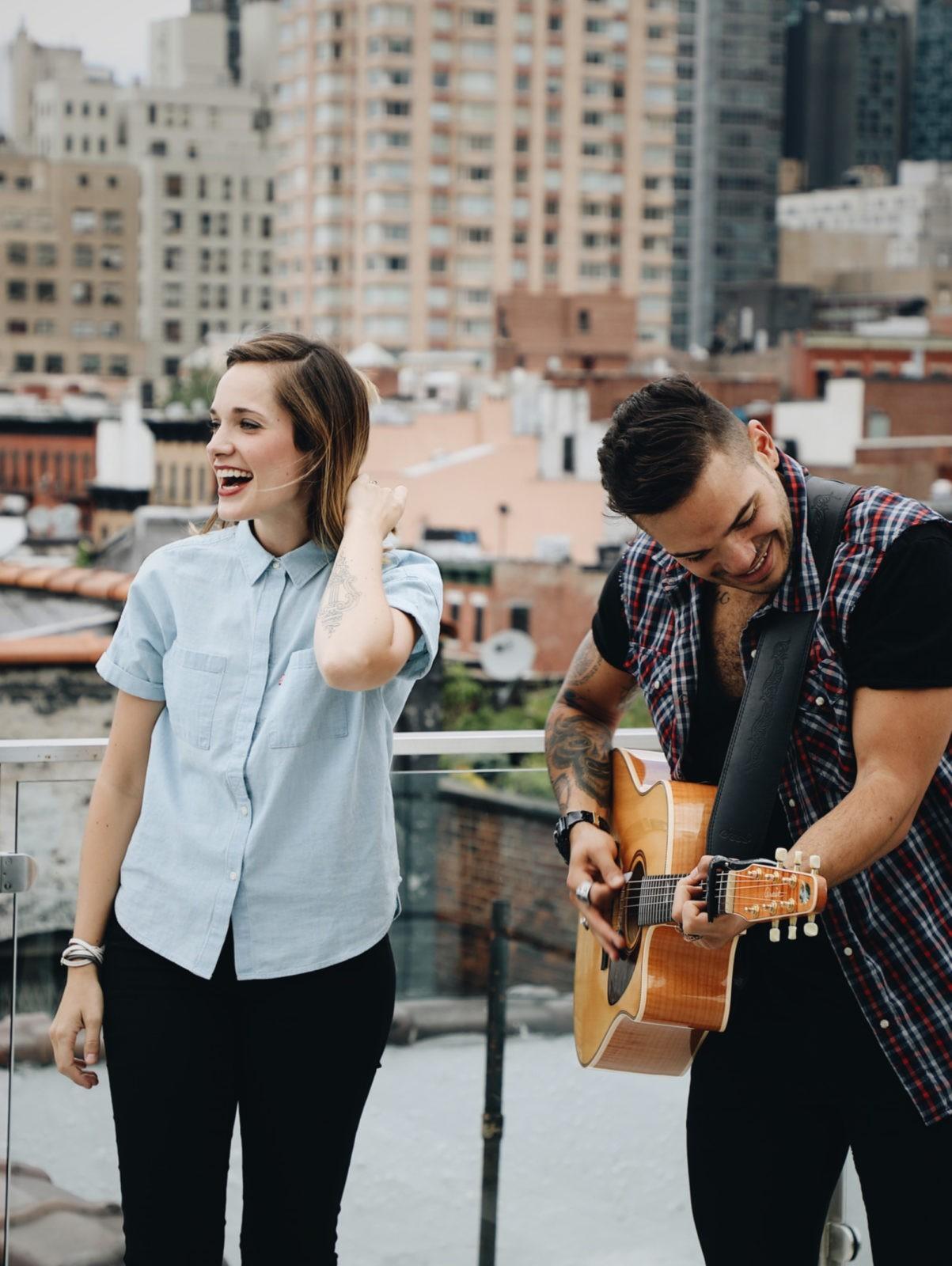 Мужчина играет на гитаре для своей девушке