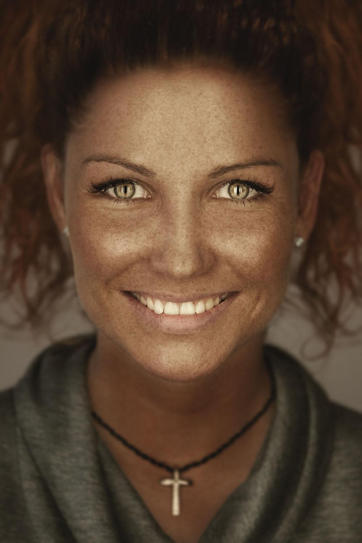 Девушка с веснушками, рыжими вьющимися волосами и зелёными глазами.