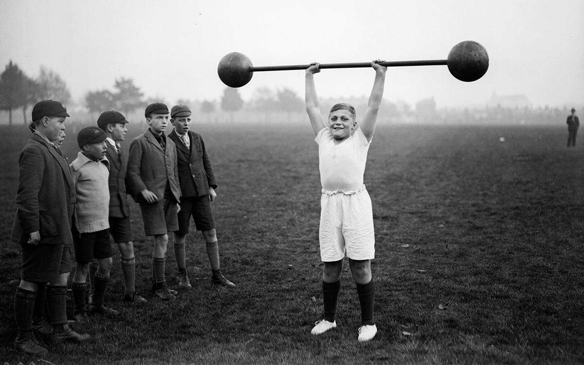 Ребёнок поднимает штангу в 1930-х годах